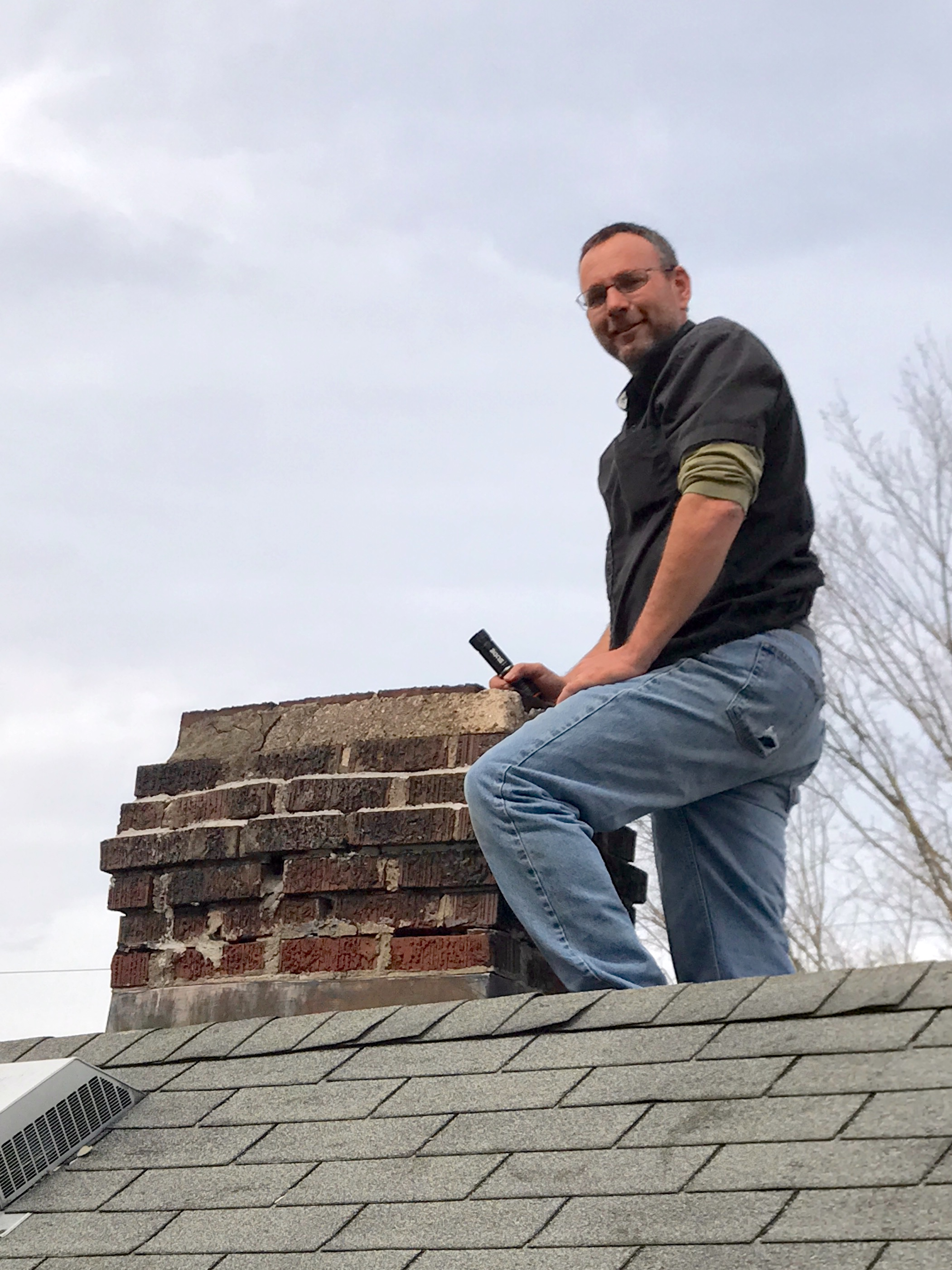 John Lawson of Assured Home Inspections inspecting the chimney and roof of a single-family home in Northern Kentucky