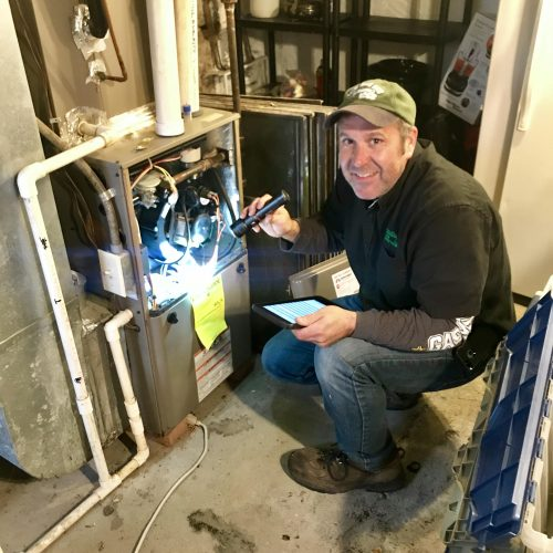Wayne Mitchell of Assured Home Inspections inspecting the furnace of a single family home
